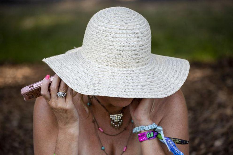 A woman uses a cellphone at Lollapalooza this summer. New phone models must be tested for radiofrequency radiation before coming to market. (Camille Fine / Chicago Tribune)